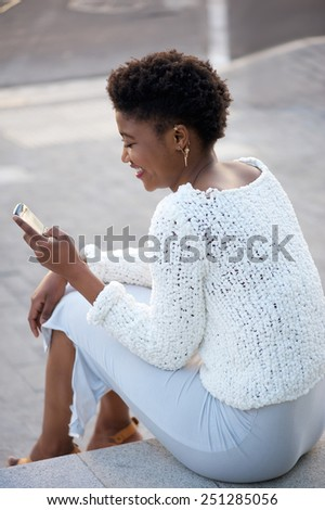 Happy young woman sitting down outside sending text message on cellphone - stock photo