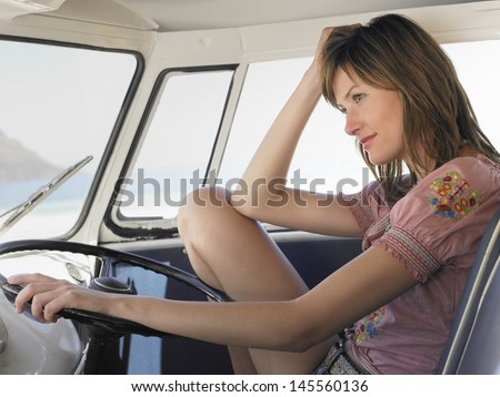 Happy young woman sitting in driver's seat of campervan