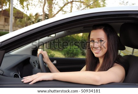 Happy young woman sitting in her new car and smiling - stock photo
