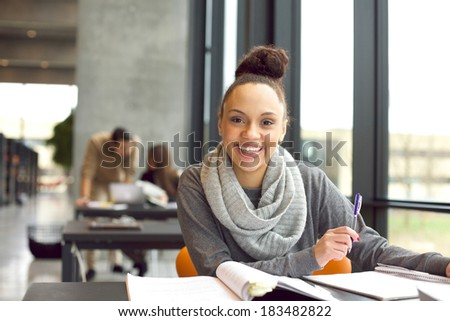 Happy young woman sitting in the library with books. Cheerful young student preparing for final exams. - stock photo