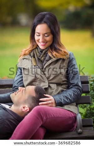 Happy young woman sitting on a bench in a park with her boyfriend lying on her lap