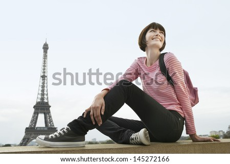Happy young woman sitting on balcony in front of Eiffel Tower - stock photo