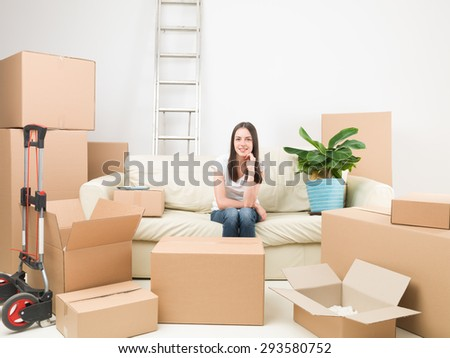 happy young woman sitting on sofa surounded by cardboard boxes in her new house - stock photo