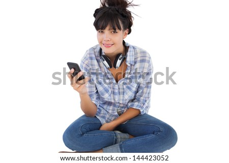 Happy young woman sitting on the floor with headphones holding her mobile phone on white background - stock photo
