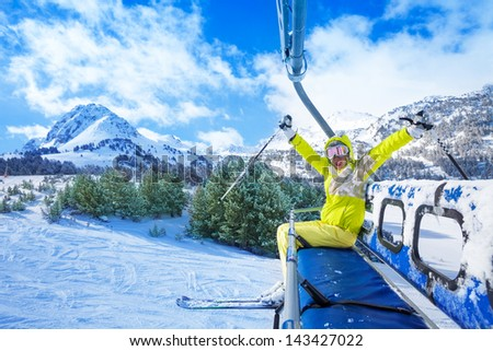 Happy young woman sitting on the ski lift chair with lifted hands and smile with mountains on background - stock photo