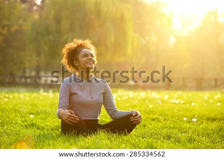 Happy young woman sitting outdoors in yoga position - stock photo