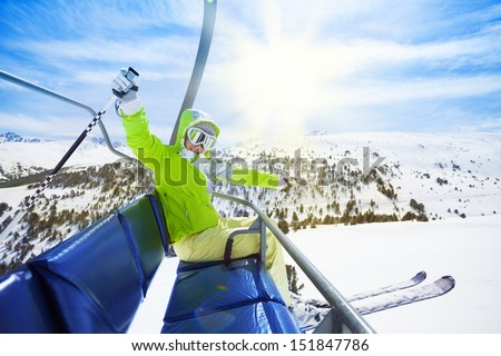 Happy young woman skier sitting on ski lift chair, smiling and happily lifting her hands - stock photo