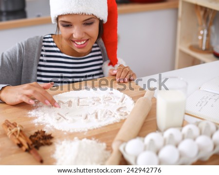 Happy young woman smiling happy having fun with Christmas preparations wearing Santa hat - stock photo