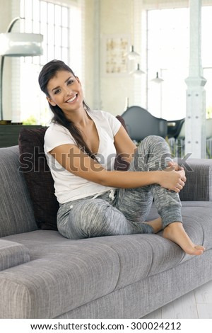 Happy young woman smiling, looking at camera, sitting on sofa at home. - stock photo