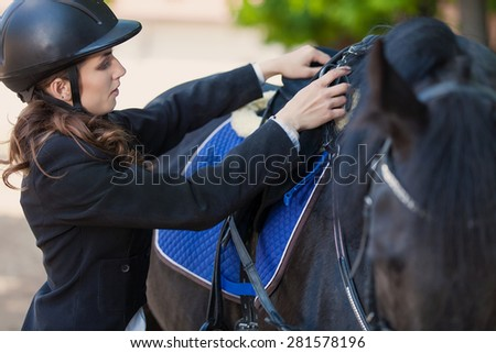 happy young woman smiling outside with her horse