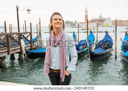 Happy young woman standing on embankment in venice, italy