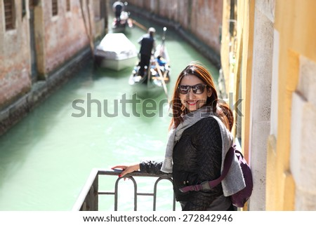 Happy young woman standing on piazza san marco in venice, italy and looking on copy space