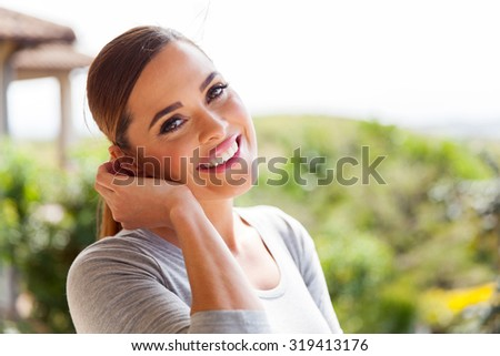 happy young woman standing outdoors - stock photo