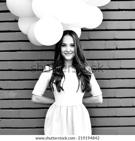 Happy young woman standing over red brick wall and holding pink and white balloons. Pleasure. Dreams. Black and white. - stock photo