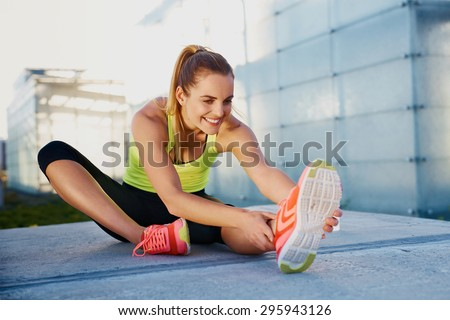 Happy young woman stretching before running outdoors - stock photo