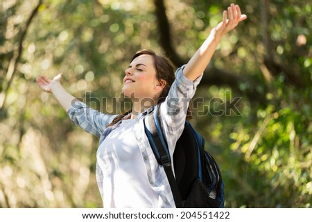 happy young woman taking deep breath in the jungle - stock photo