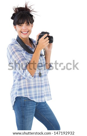 Happy young woman taking picture with her camera on white background