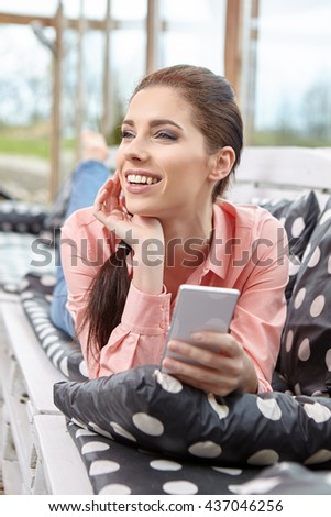 Happy young woman taking smartphone selfie photo with smart phone on outdoor patio sofa furniture. Beautiful woman at hotel resort terrace smiling for picture enjoying modern luxury living - stock photo