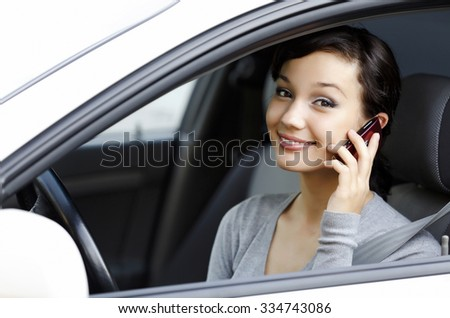 happy young woman talk on cell phone sitting in white car  - stock photo