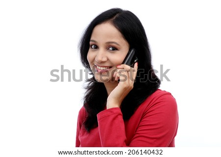 Happy young woman talking on mobile phone against white background