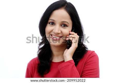 Happy young woman talking on mobile phone against white background - stock photo