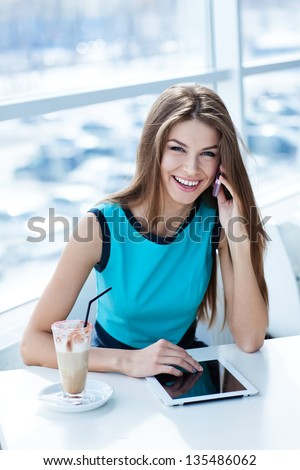 happy young woman talking on the cell phone and using tablet computer in a coffee shop - stock photo