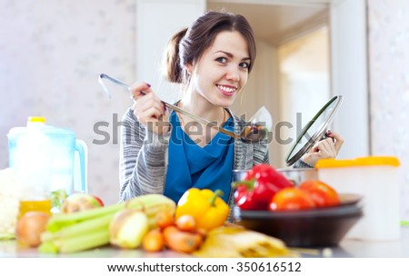 Happy young woman tests food with ladle in the kitchen at home - stock photo