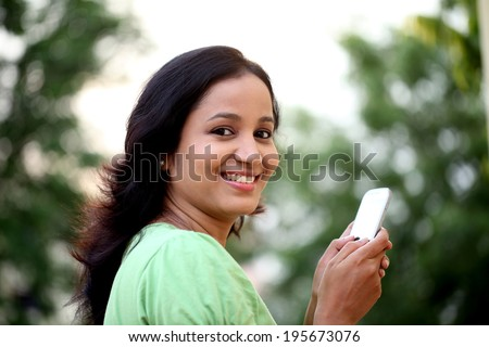 Happy young woman text messaging at outdoors - stock photo