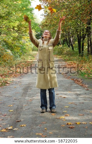 Happy young woman tosses up yellow leaves - stock photo