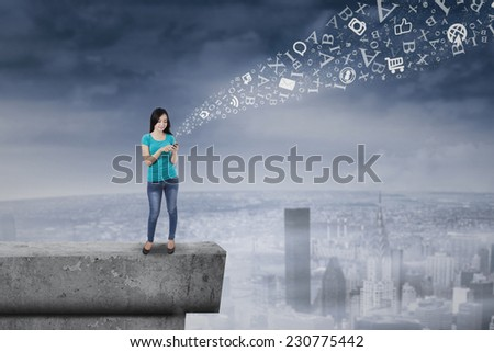 Happy young woman touching and browsing her smart phone on rooftop - stock photo
