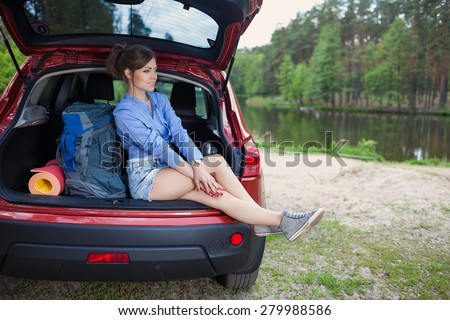 Happy young woman tourist travel on a red car to summer forest. Holiday trip to lake