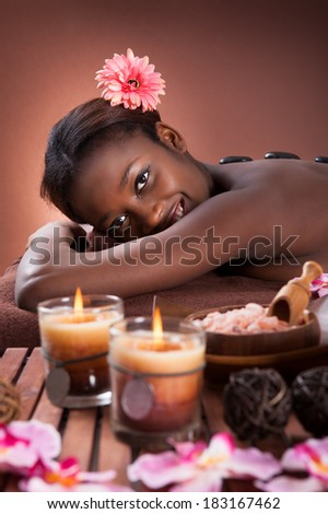 Happy young woman undergoing lastone therapy at beauty spa - stock photo