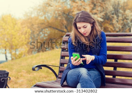 Happy young woman using a mobile phone outdoors in the fall. - stock photo