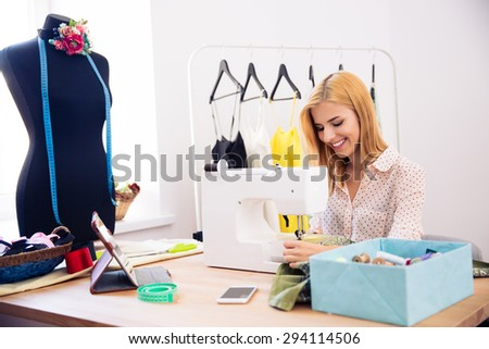 Happy young woman using a sewing machine in laundry - stock photo