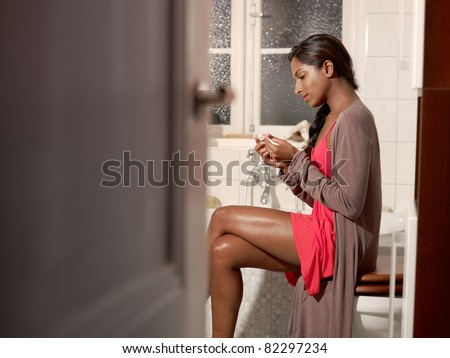 Happy young woman using pregnancy test in bathroom. Horizontal shape, copy space