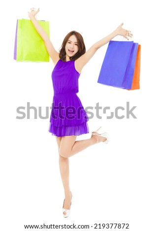 happy young woman walking and holding shopping bags over white background