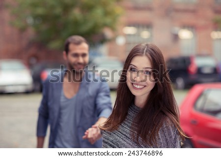 Happy young woman walking in an urban street with her boyfriend turning to smile at the camera - stock photo