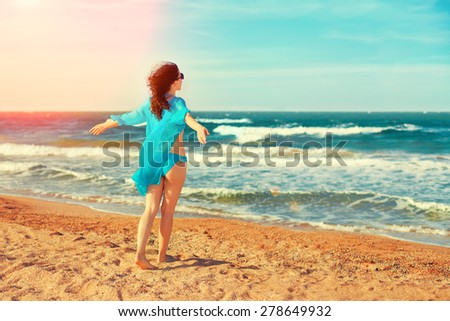 Happy young woman walking on the beach - stock photo