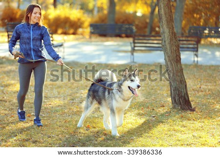Happy young woman walking with her dog in park - stock photo