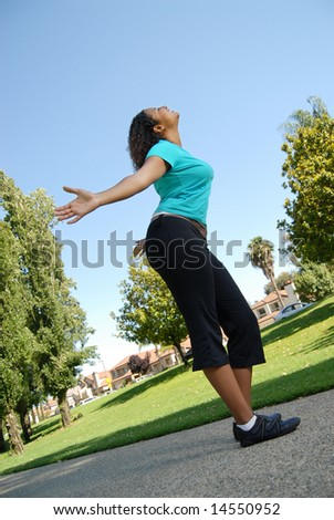 Happy young woman walking with open arms - stock photo