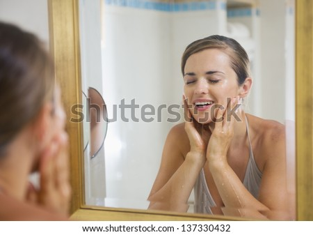 Happy young woman washing face in bathroom - stock photo