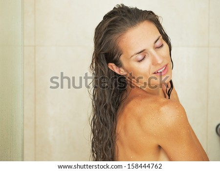 Happy young woman washing in shower - stock photo