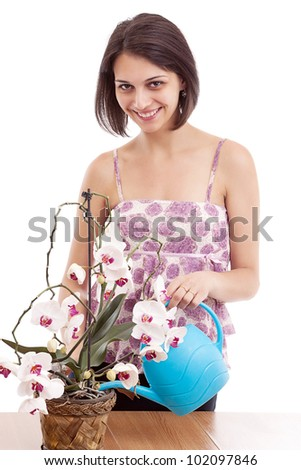 Happy young woman watering orchid using sprinkling can - stock photo
