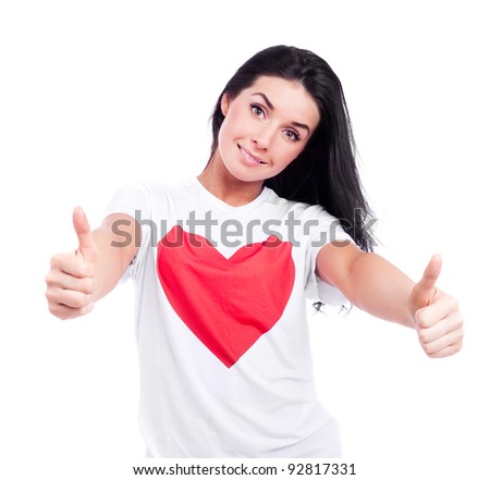 happy young  woman wearing a T-shirt with a big red heart with two thumbs up, isolated against white background
