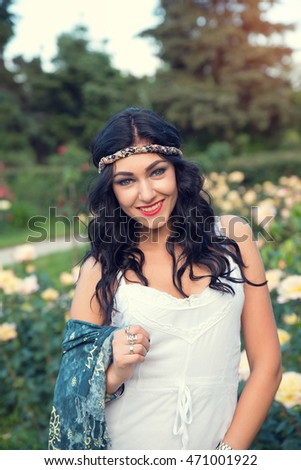 Happy young woman wearing boho style clothes enjoy in summer day amid the green park. Beautiful hippie girl.