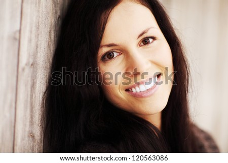 Happy young woman wearing brown cardigan is smiling, outside in winter day. Pretty woman with long hair. - stock photo