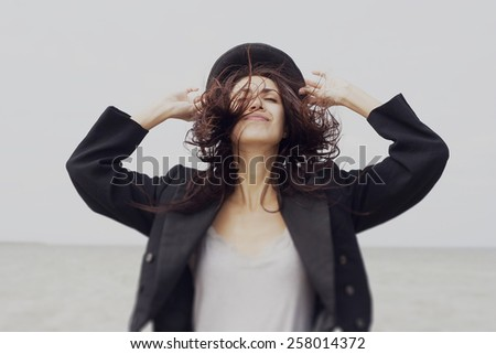 Happy young woman wears cylinder and tail coat - stock photo