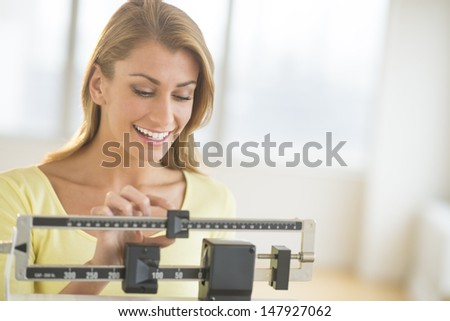 Happy young woman weighing herself on balance scale at health club - stock photo