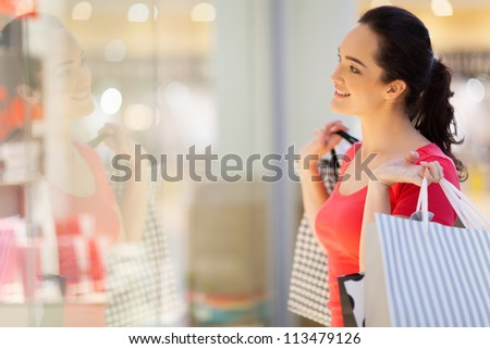 happy young woman window shopping - stock photo