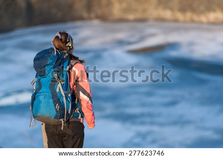 Happy young woman with a backpack standing on the shore of the lake - stock photo